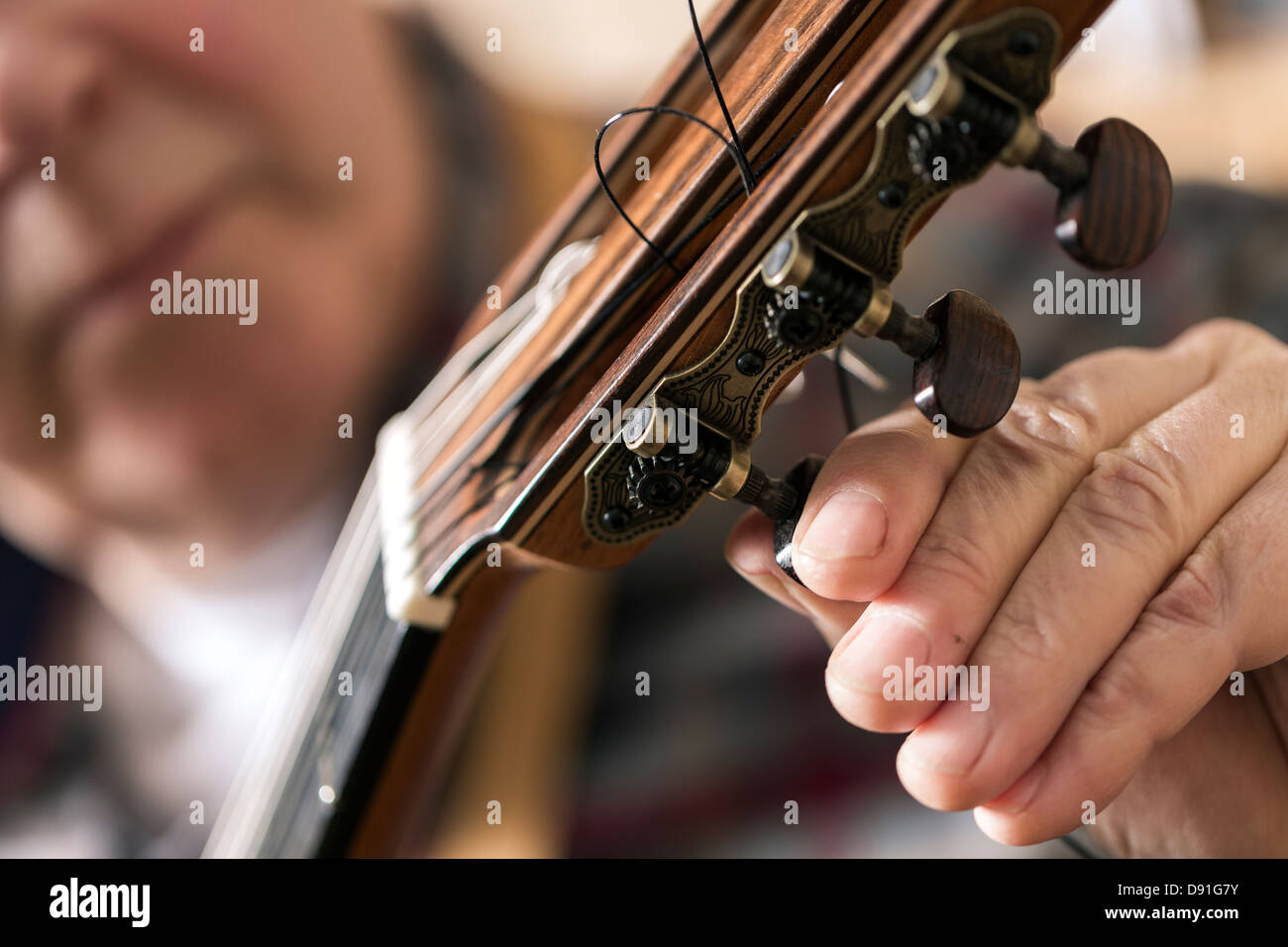Close up of guitar maker tuning and testing acoustic guitar in workshop - Stock Image