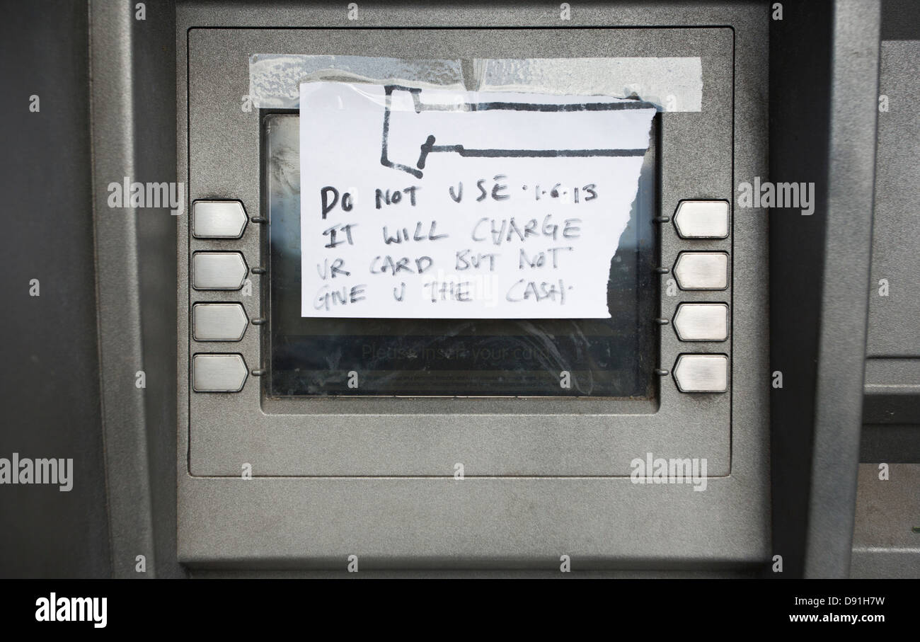 Out of order cash machine ATM with a hand written note covering the screen warning against using a bank card to - Stock Image