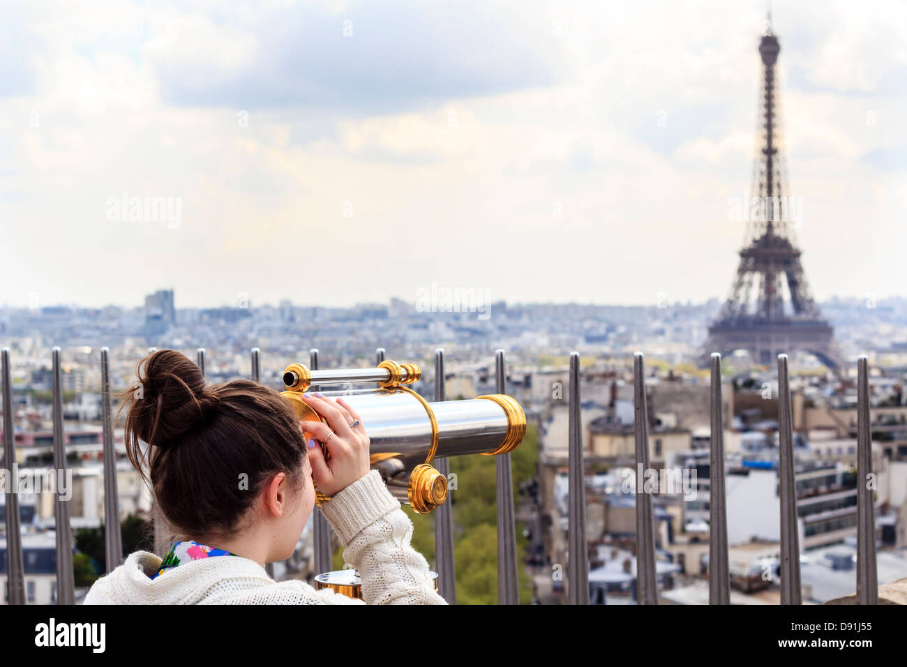 Girl looking at the Eiffel Tower through observation telescope on the rooftop of the Arc de Triump - Stock Image