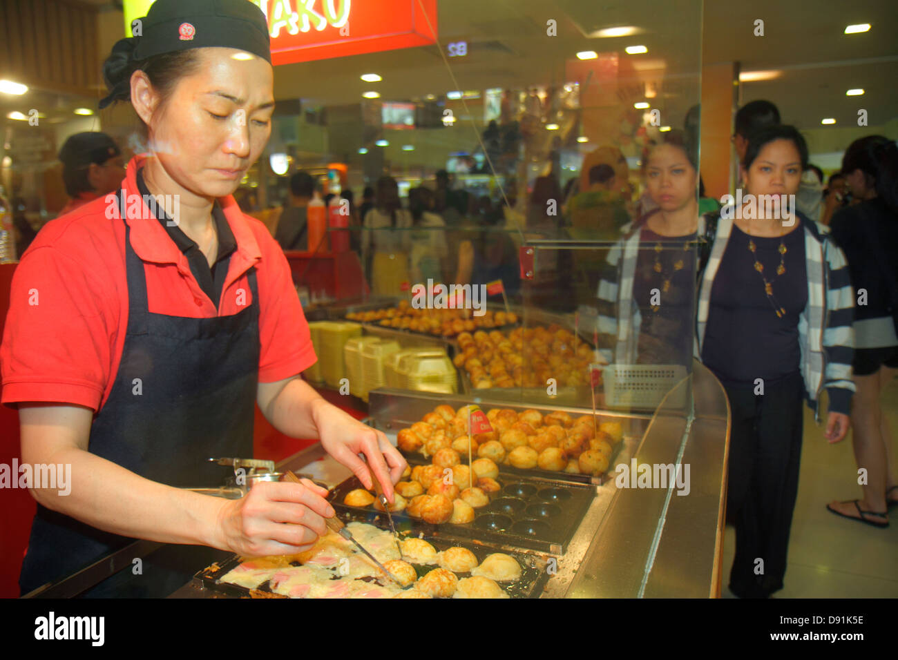 Singapore Orchard Road Plaza Singapura shopping mall complex food court Asian woman restaurant employee cook job - Stock Image