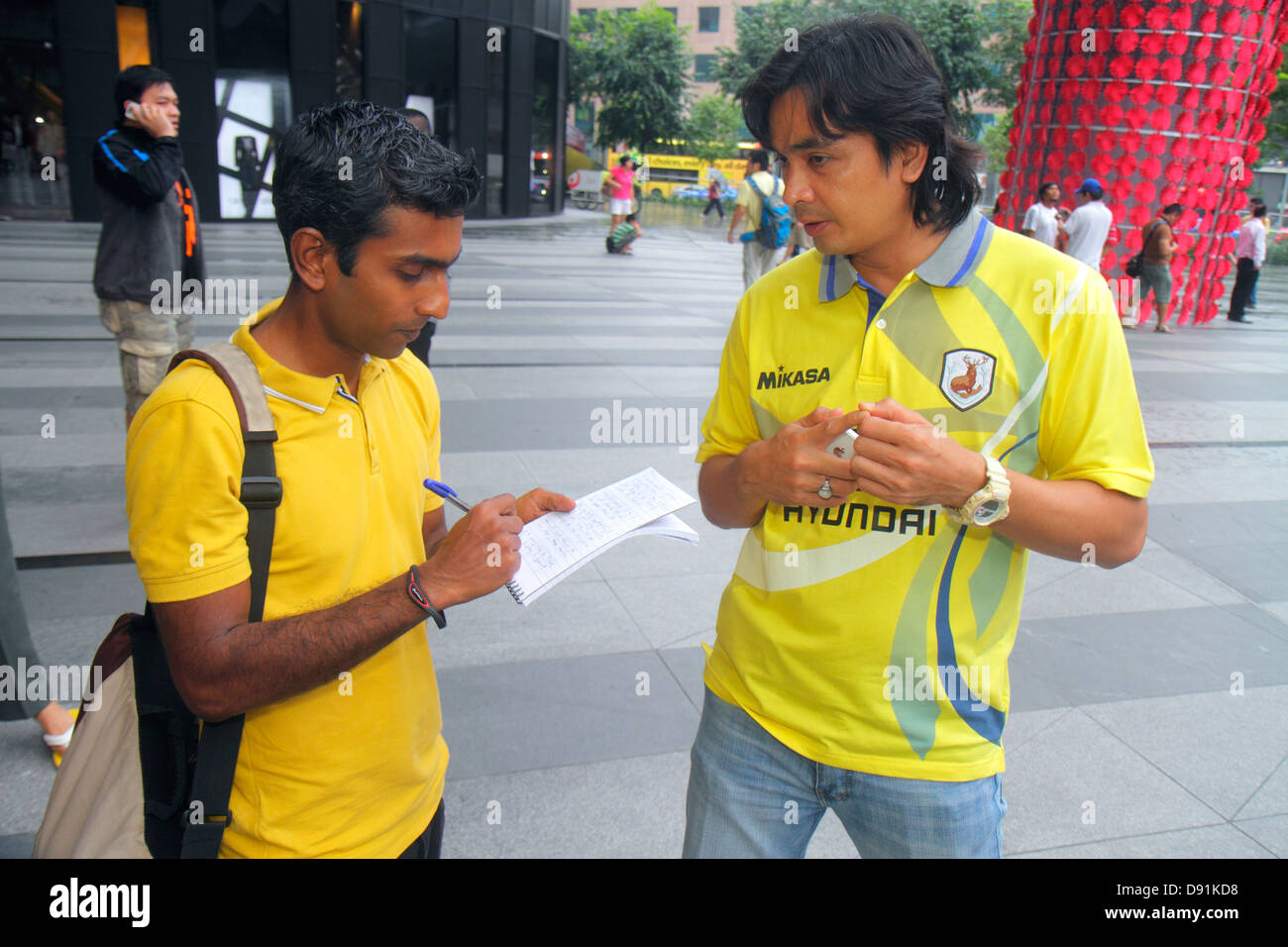 Singapore Orchard Road Asian reporter interview interviewing writing taking notes Grand Prix promotion driver Spanish - Stock Image