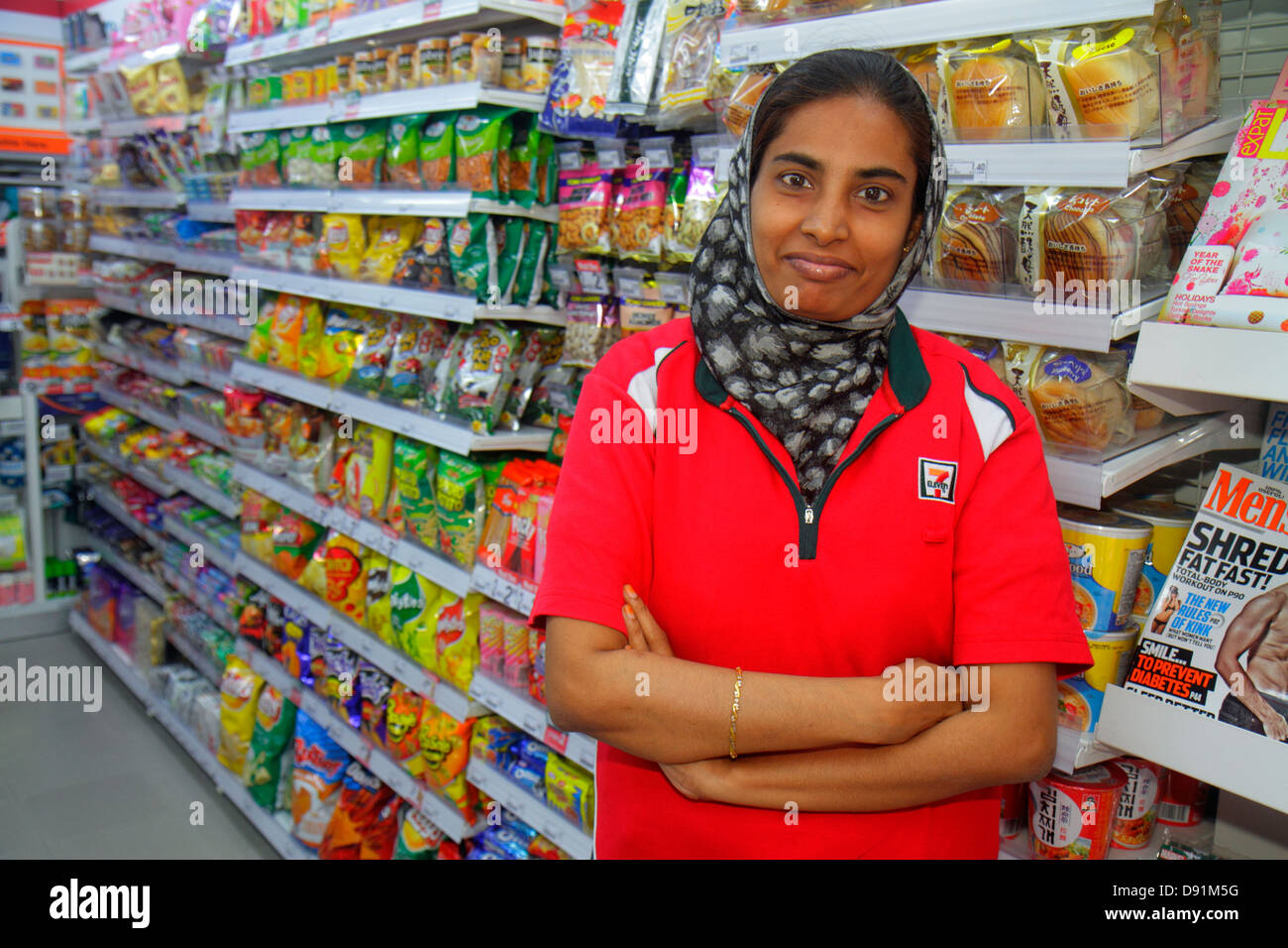 Singapore Kampong Glam Muslim Quarter Arab Street 7-Eleven convenience store business inside interior Asian woman - Stock Image