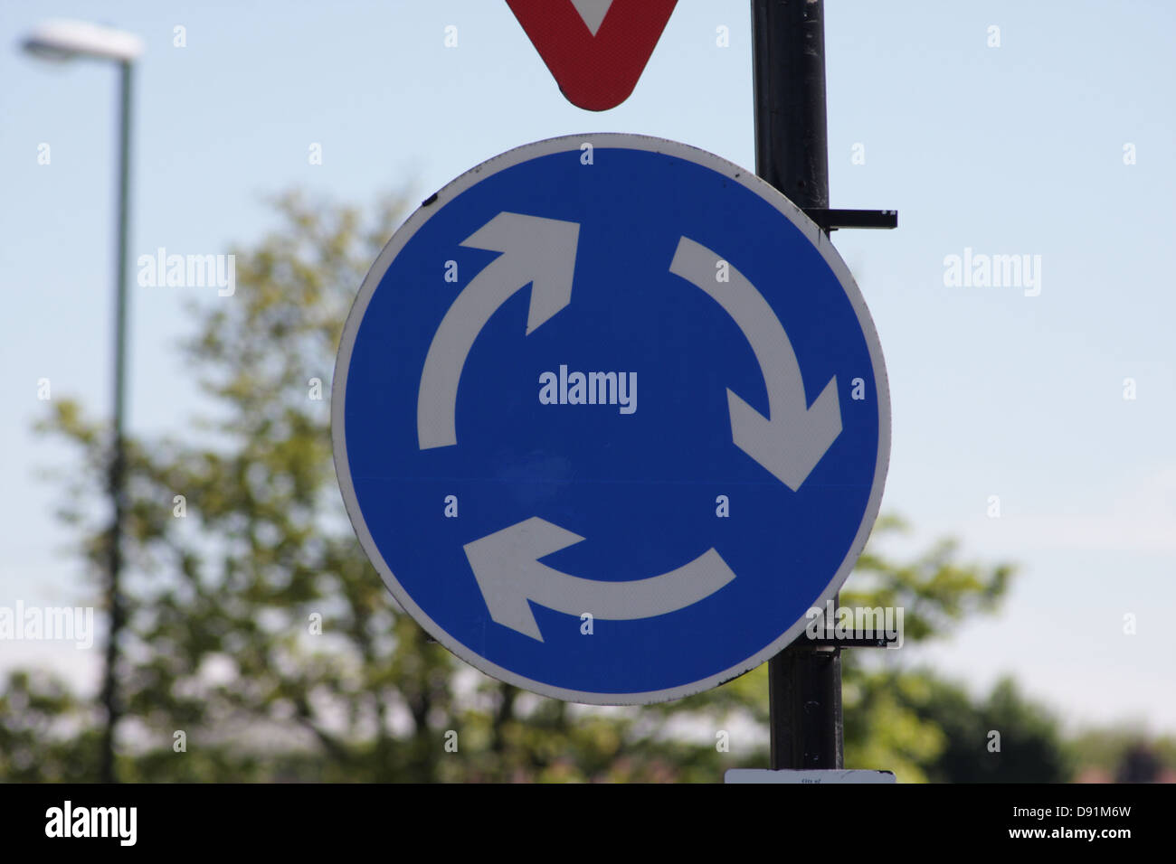 Mini Roundabout road sign. A British highway code sign, a round circle with arrows indicating a mini roundabout - Stock Image
