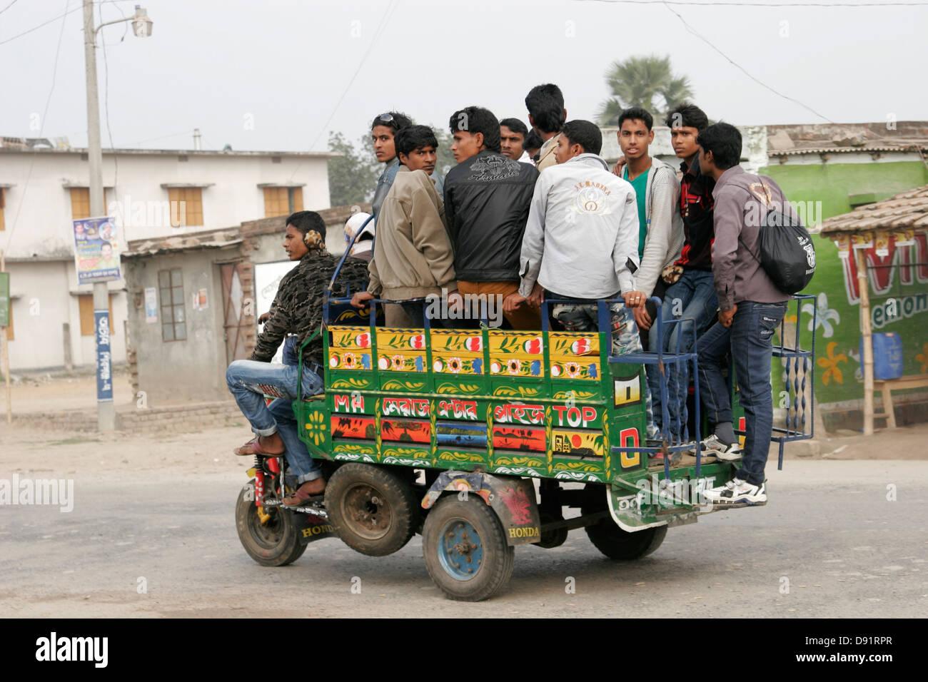 Tiny motor vehicle carrying a group of Bangladeshi men on the road in rural Bangladesh - Stock Image