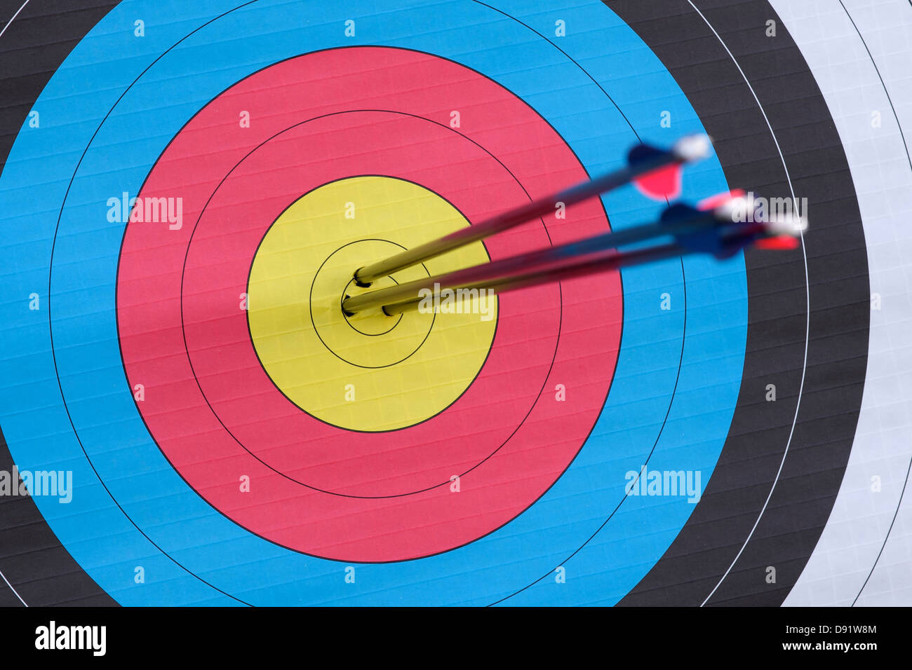 Three Arrows Embedded In The Dead Centre Of An Archery Target Focus
