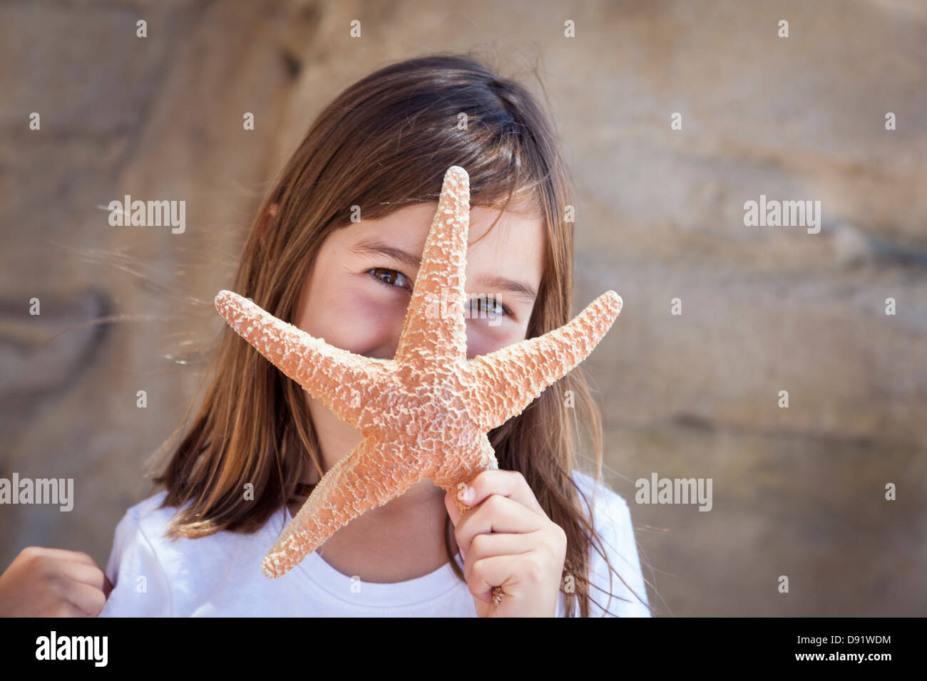 Young Pretty Girl Playing with Starfish. - Stock Image