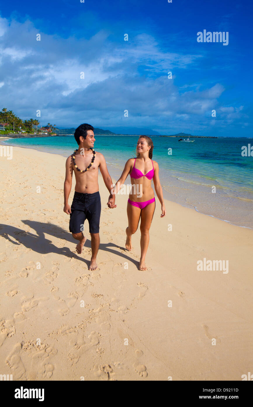 mixed couple walking on the beach in hawaii - Stock Image
