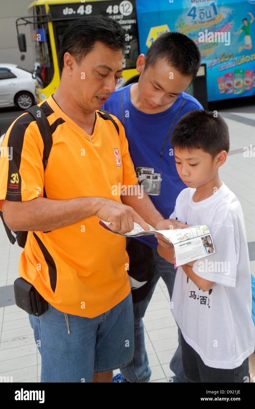 Bangkok Thailand Pathum Wan Rama 1 Road Asian man father boy son teen guide book pointing - Stock Image