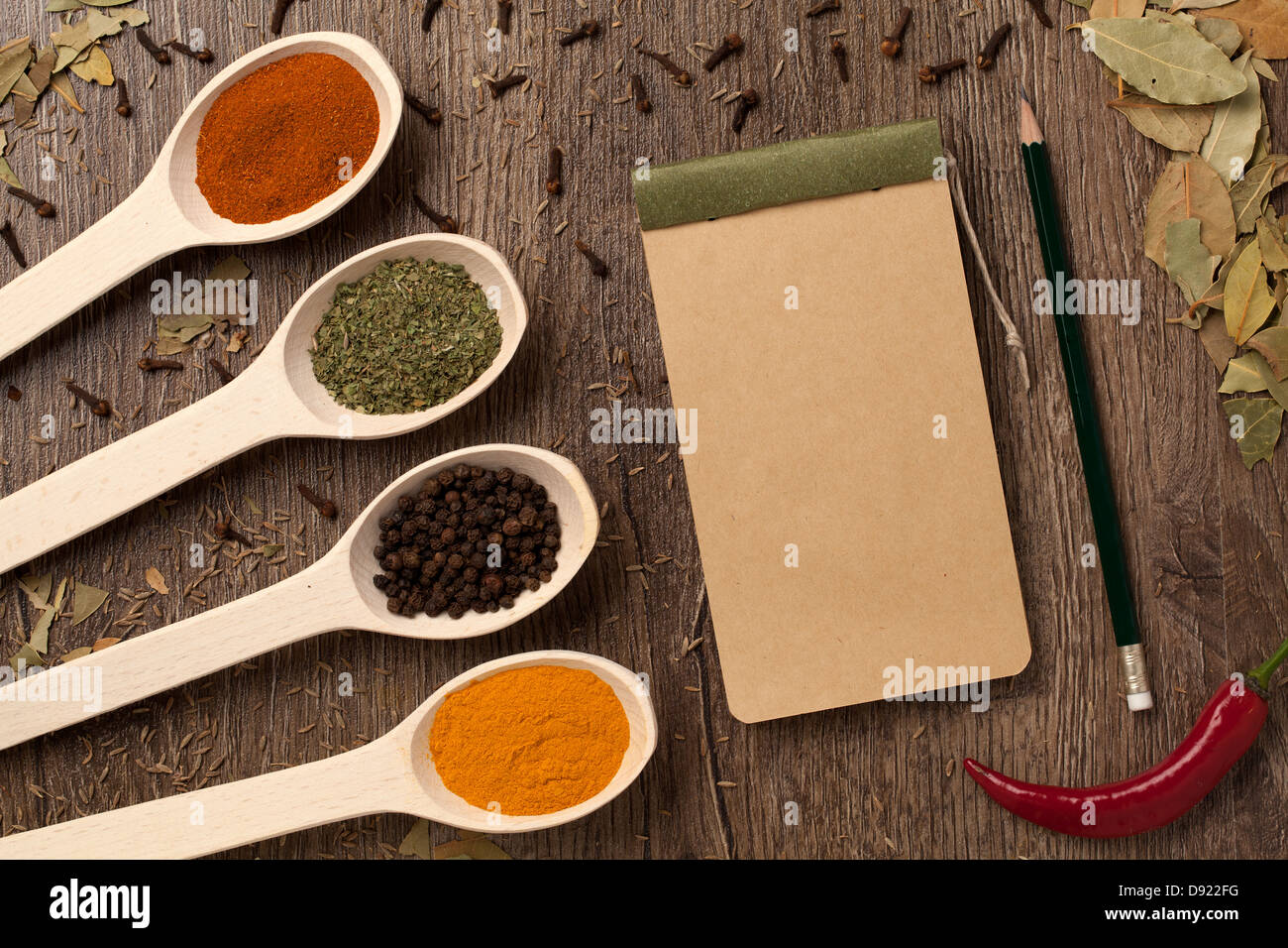 Red chili peppers, spices in spoons, notebook paper and
