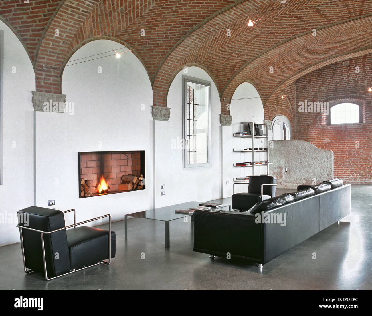 modern living room with leather black sofa , fireplace, concrete ...
