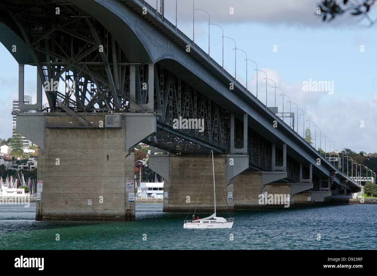 Sail boat under Auckland Harbour Bridge, New Zealand - Stock Image