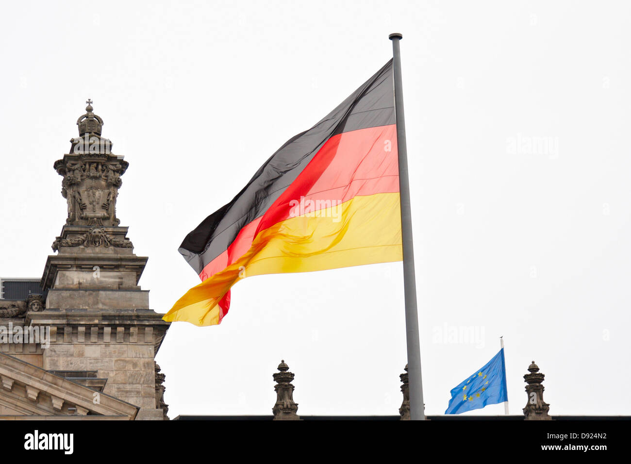 Big German flag and small EU flag on the roof of the Reichstag - Stock Image