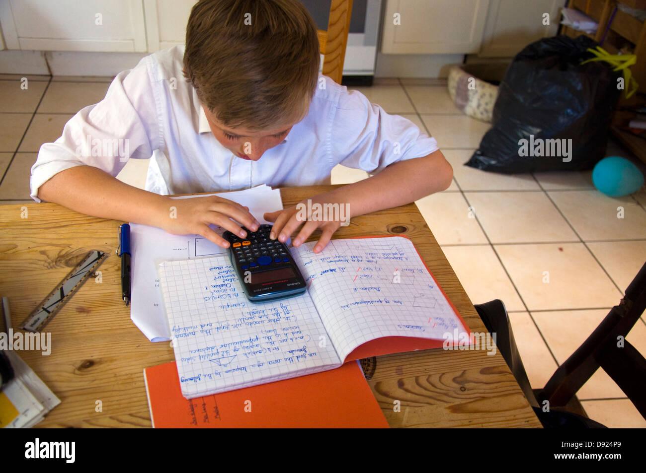 Thirteen 13 year old boy doing mathematics homework on kitchen table thirteen 13 year old boy doing mathematics homework on kitchen table using an electronic calculator workwithnaturefo