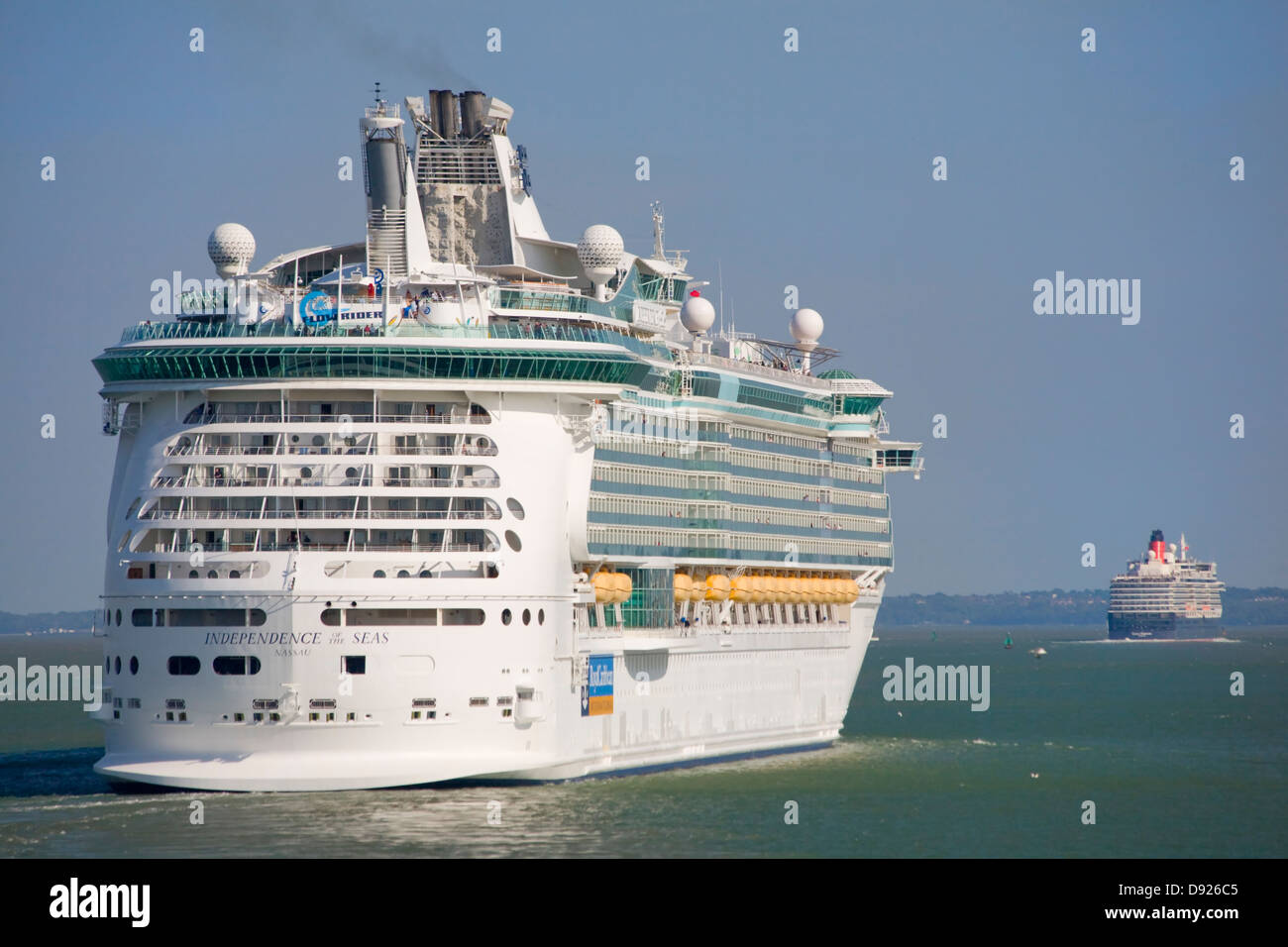 Independence of the Seas cruise ship following the Queen Elizabeth out of the Solent, Southampton - Stock Image