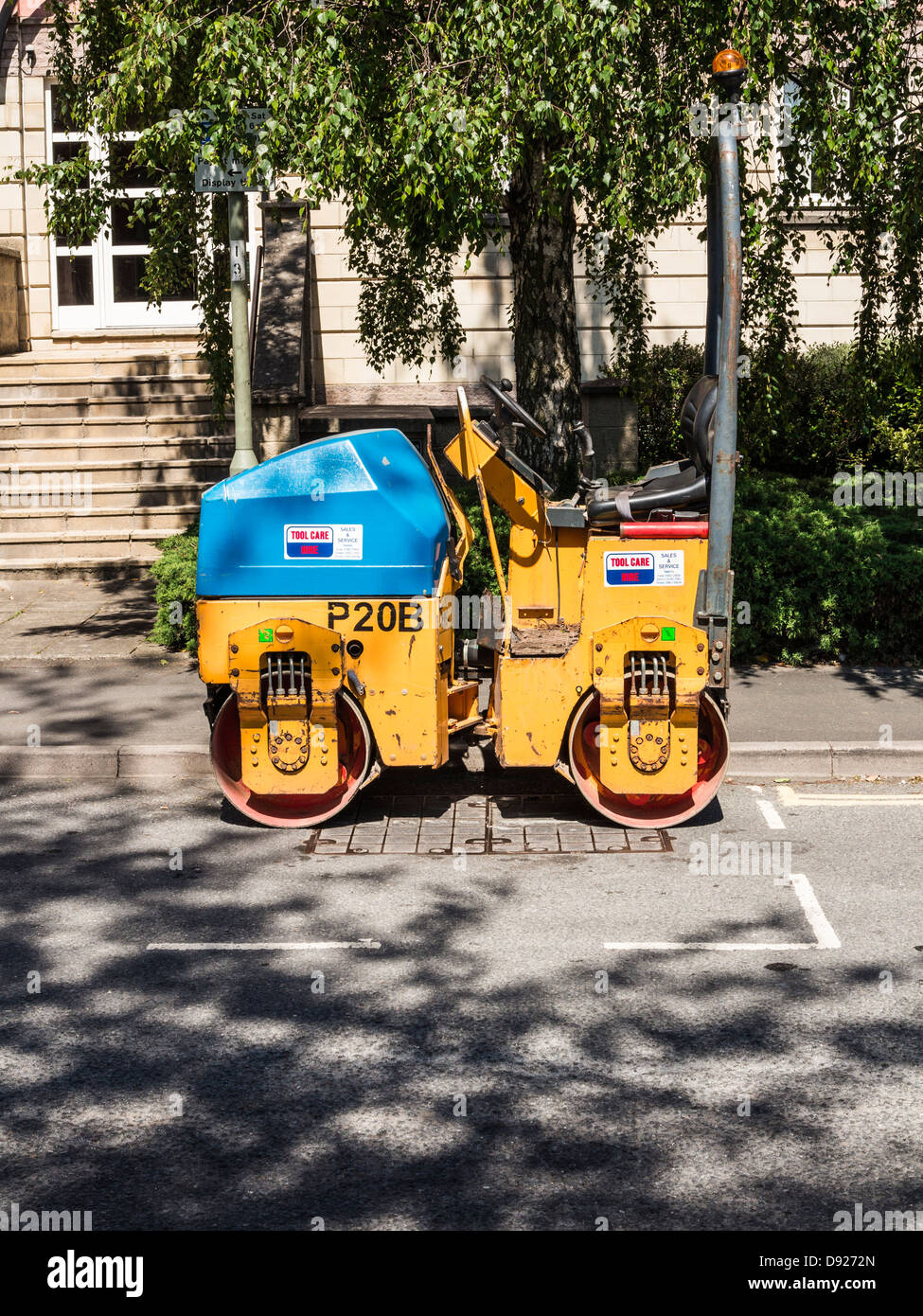 Road roller parked in parking bay on a road, Exeter, Devon, England - Stock Image