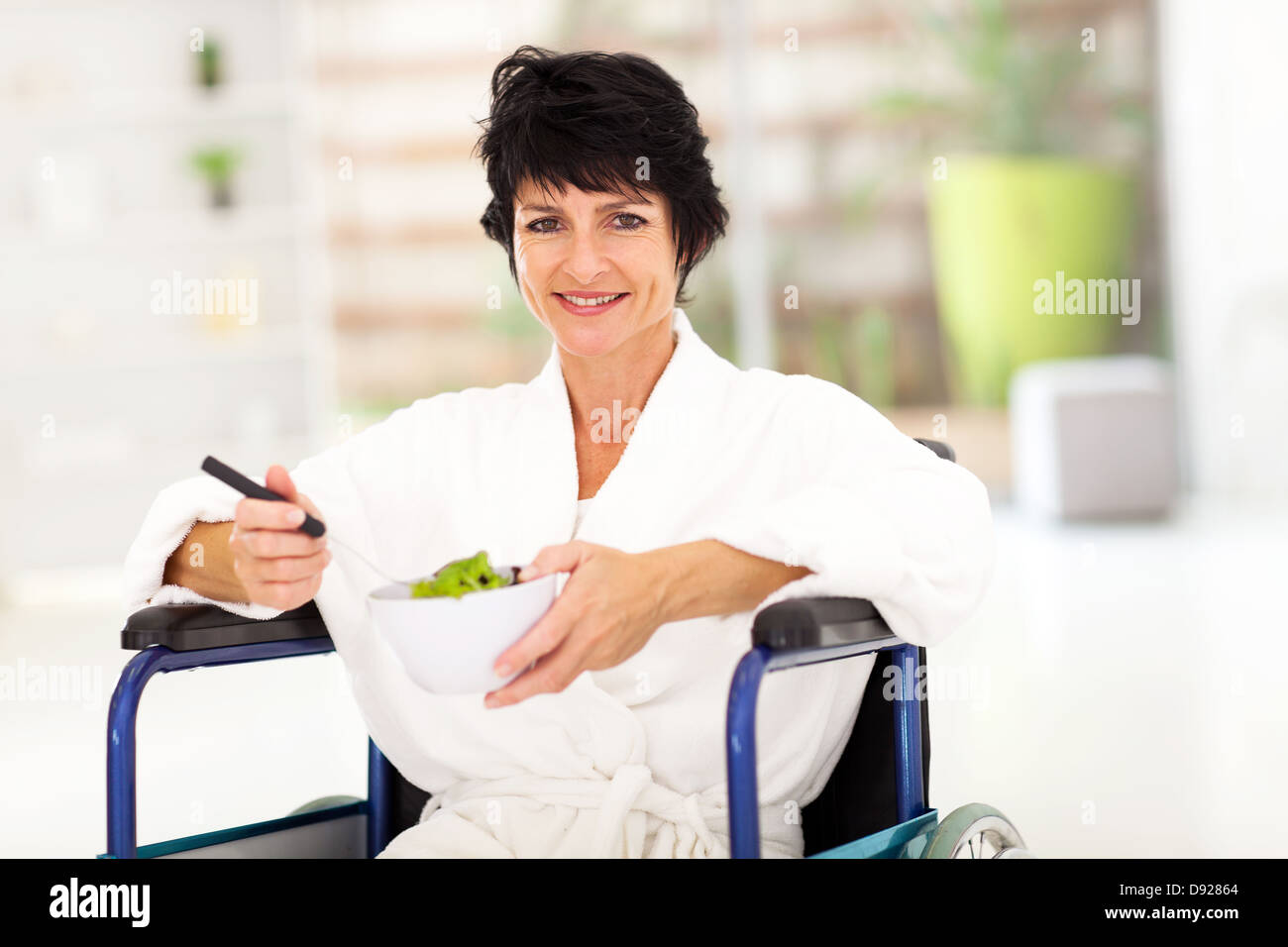 recovering middle aged woman eating salad on wheelchair - Stock Image