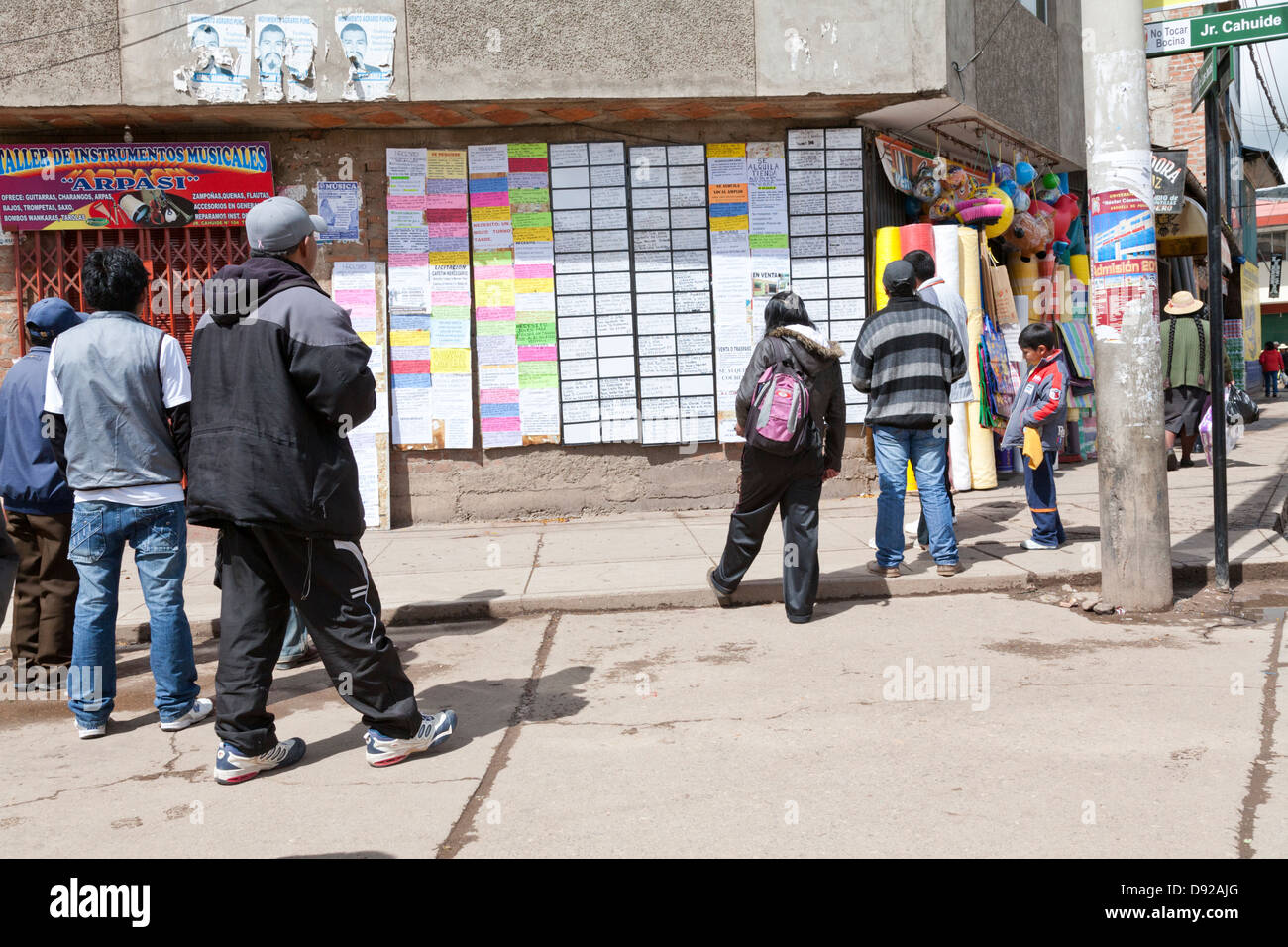 Local peruvians checking signboards for jobs, Puno, peru - Stock Image
