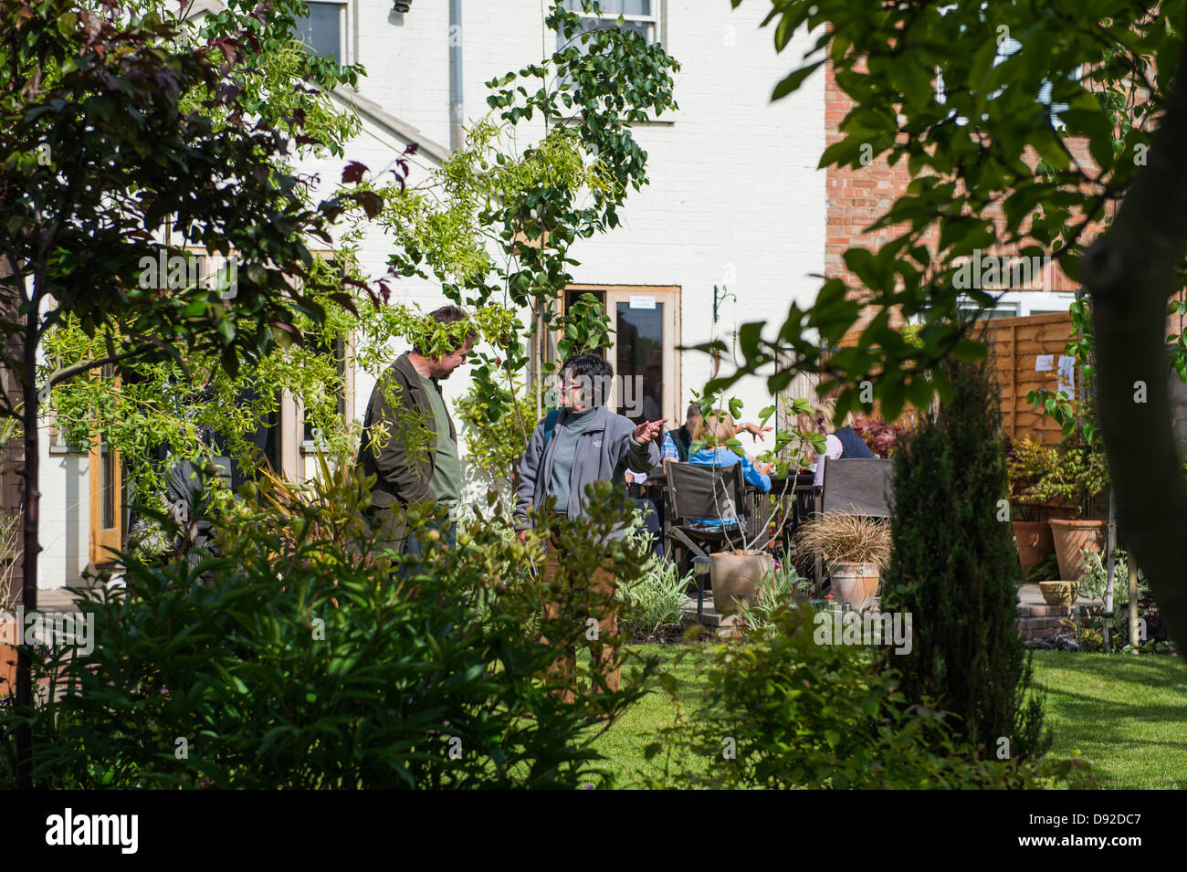 People discussing a garden at an Open Garden event in Peterborough. - Stock Image