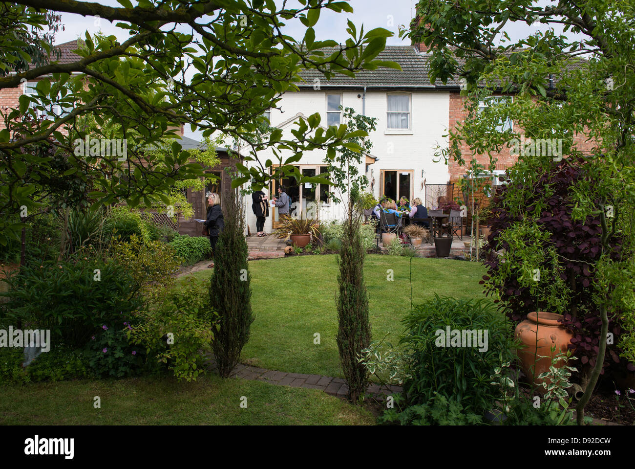 View of a garden with people enjoying the company. - Stock Image
