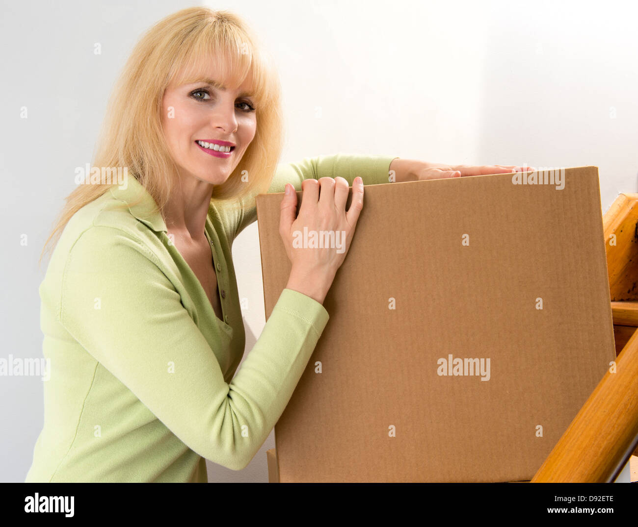 Woman pauses moving boxes up the stairs in a house - Stock Image