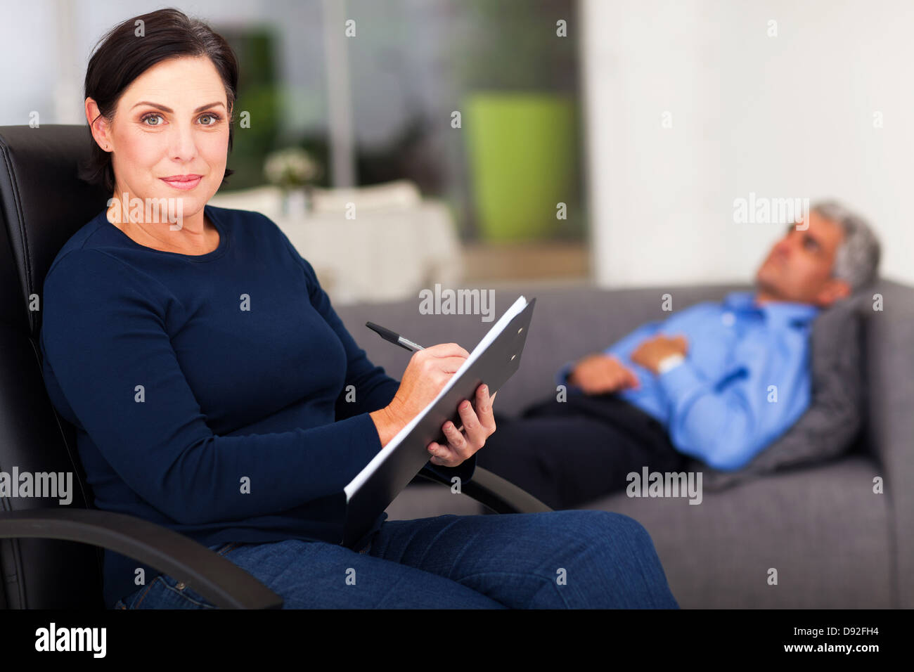 portrait of middle aged female therapist in office with patient in background - Stock Image