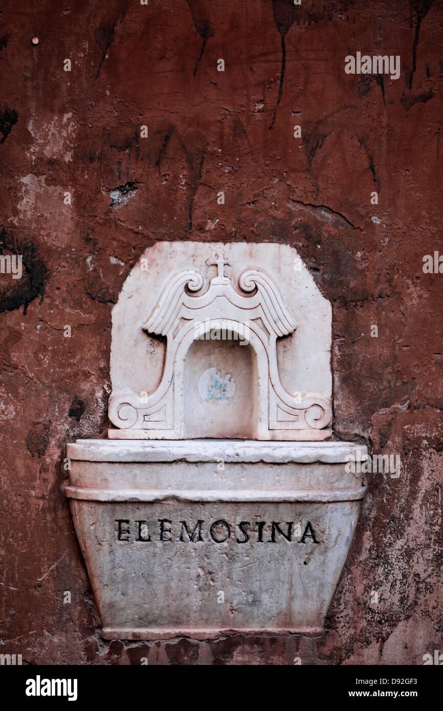 Receptacle for alms money on wall - Stock Image