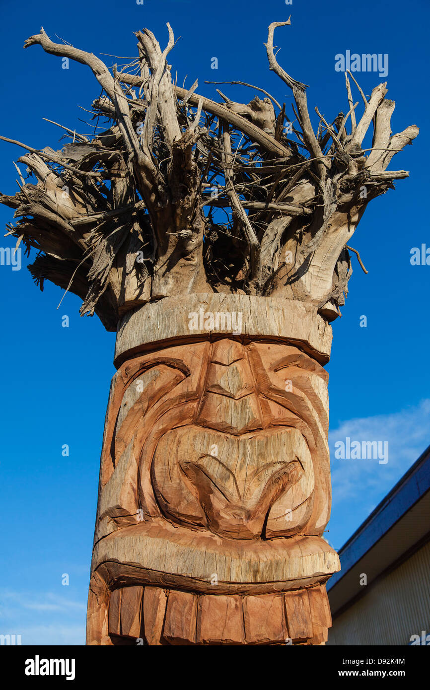 A large wooden totem carved upside down from an tree using the tangled roots as a headdress. - Stock Image