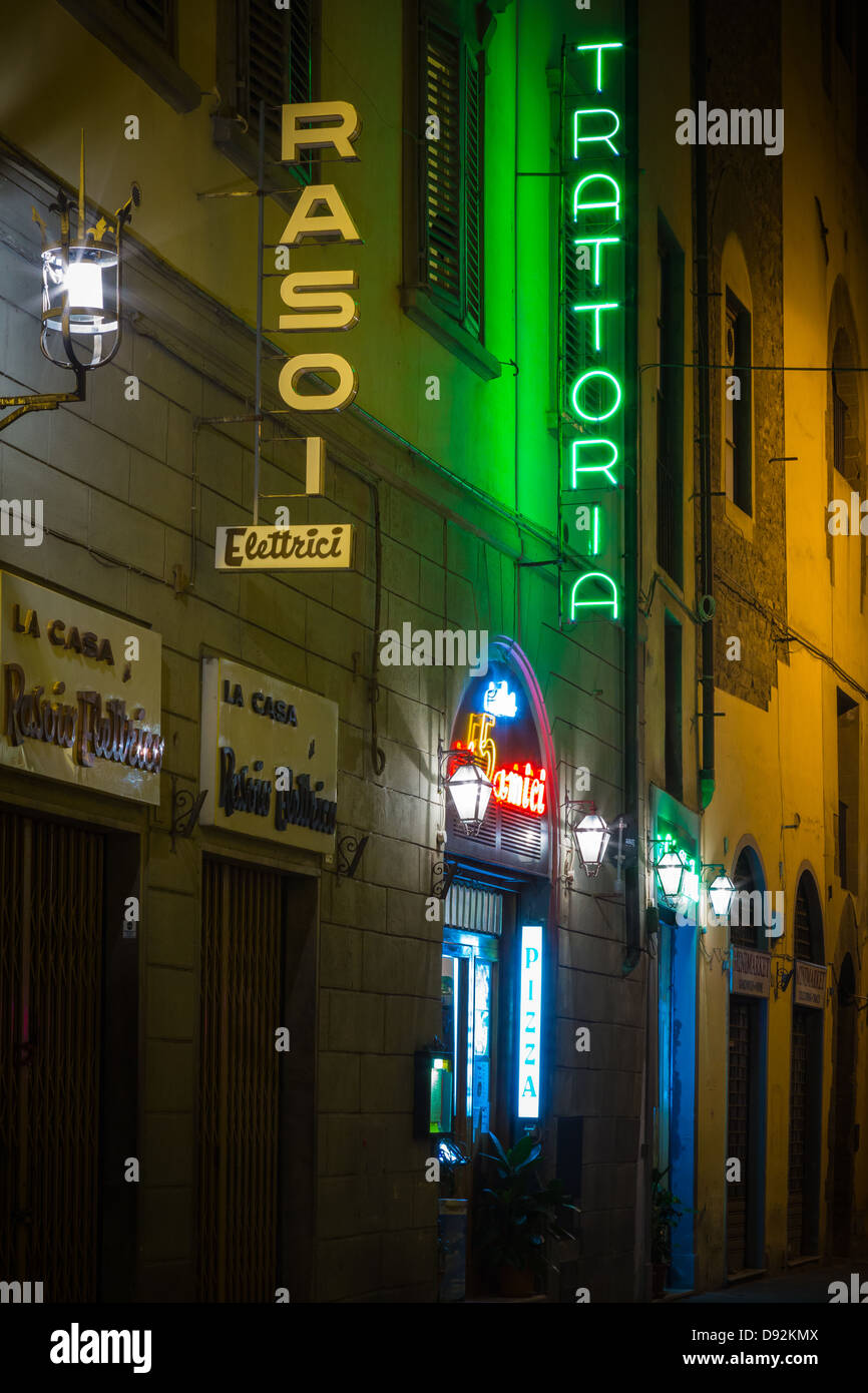Neon signs advertize establishments in the evening in the Italian city Firenze (Florence) - Stock Image