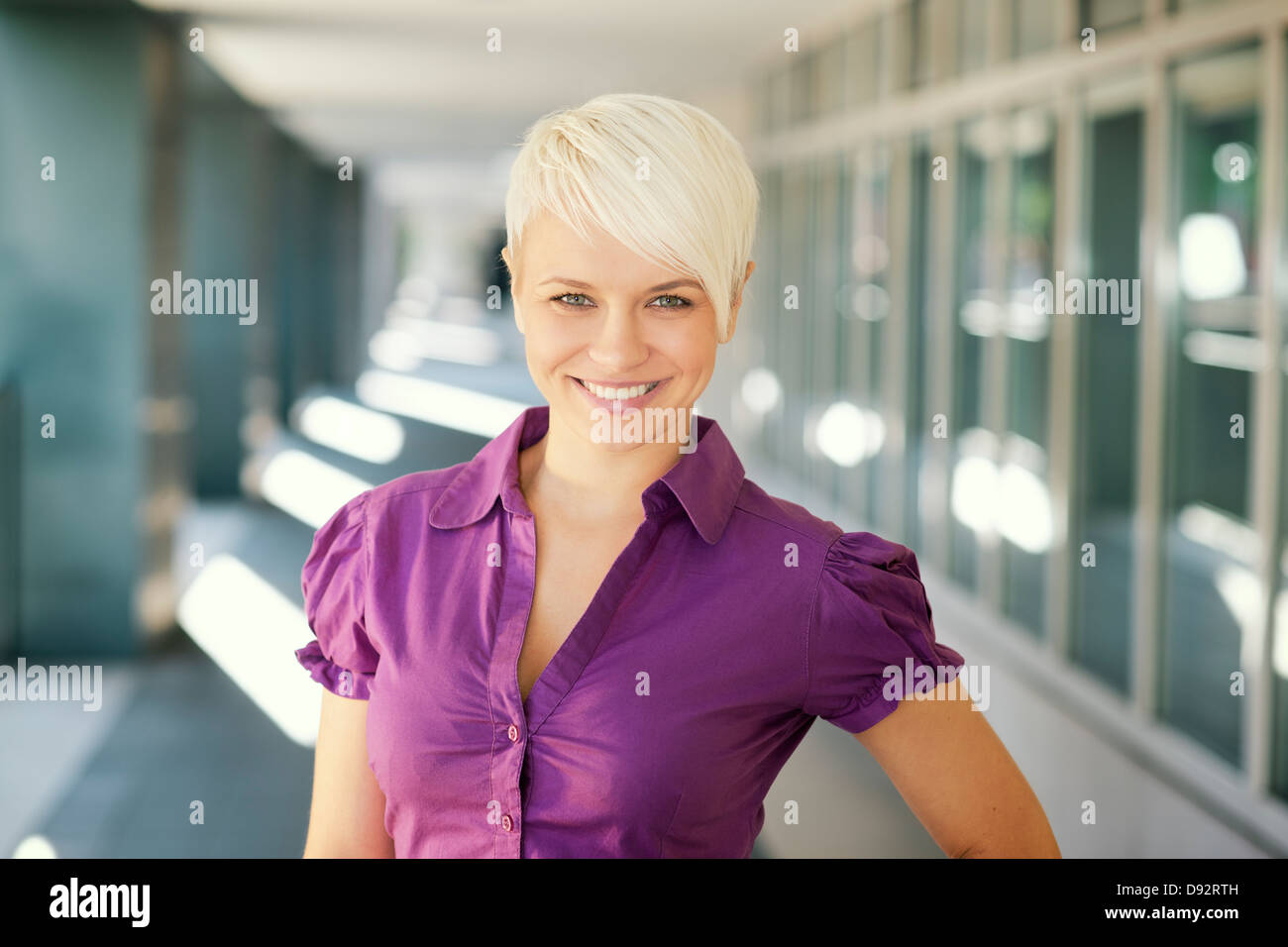 portrait of confident attractive business woman smiling and looking at camera out of office building - Stock Image