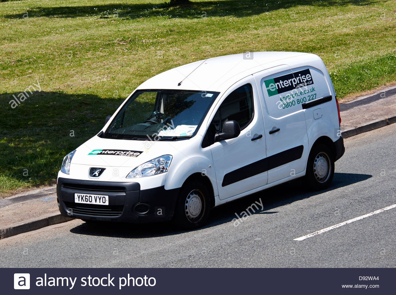 d9d06bc8b2 white peugeot van enterprise rent a car parked on the roadside - Stock Image