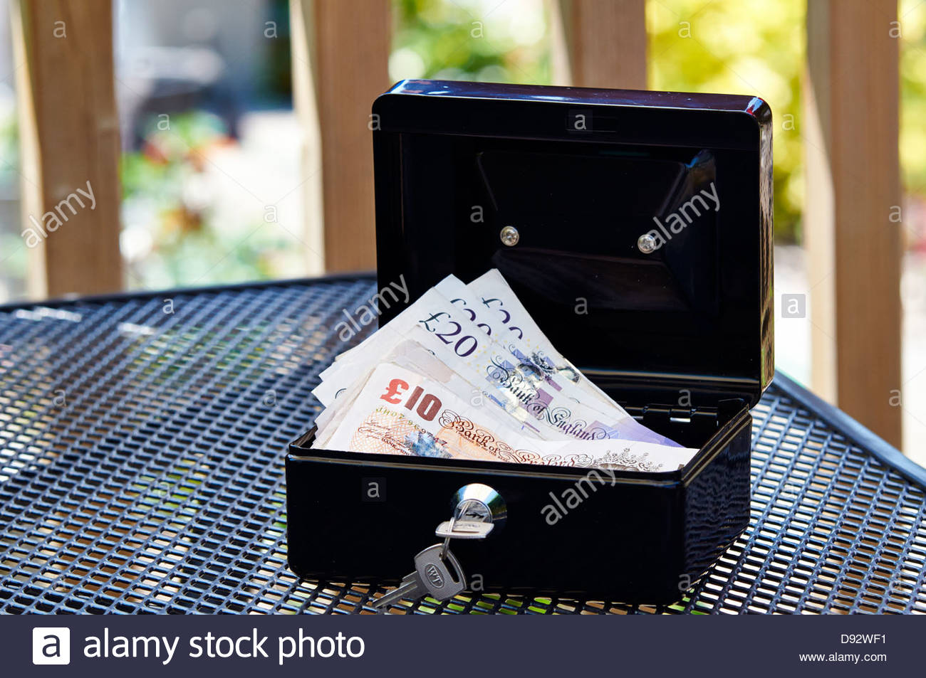 a black metal cash box with keys in lock and filled with british 10 and 20 pound notes - Stock Image