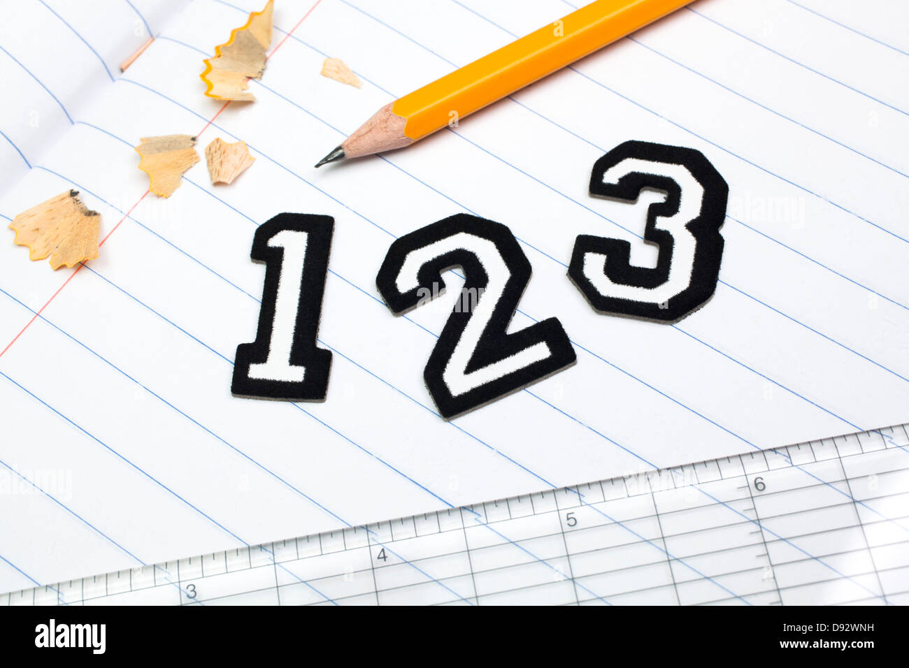 varsity font sticker numbers 1 2 3 atop a lined paper notebook