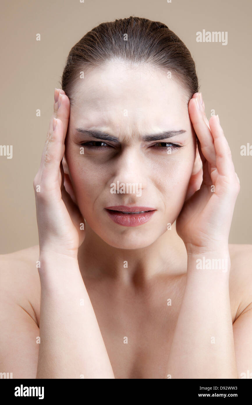 A grimacing young woman with her hands to her temples Stock Photo