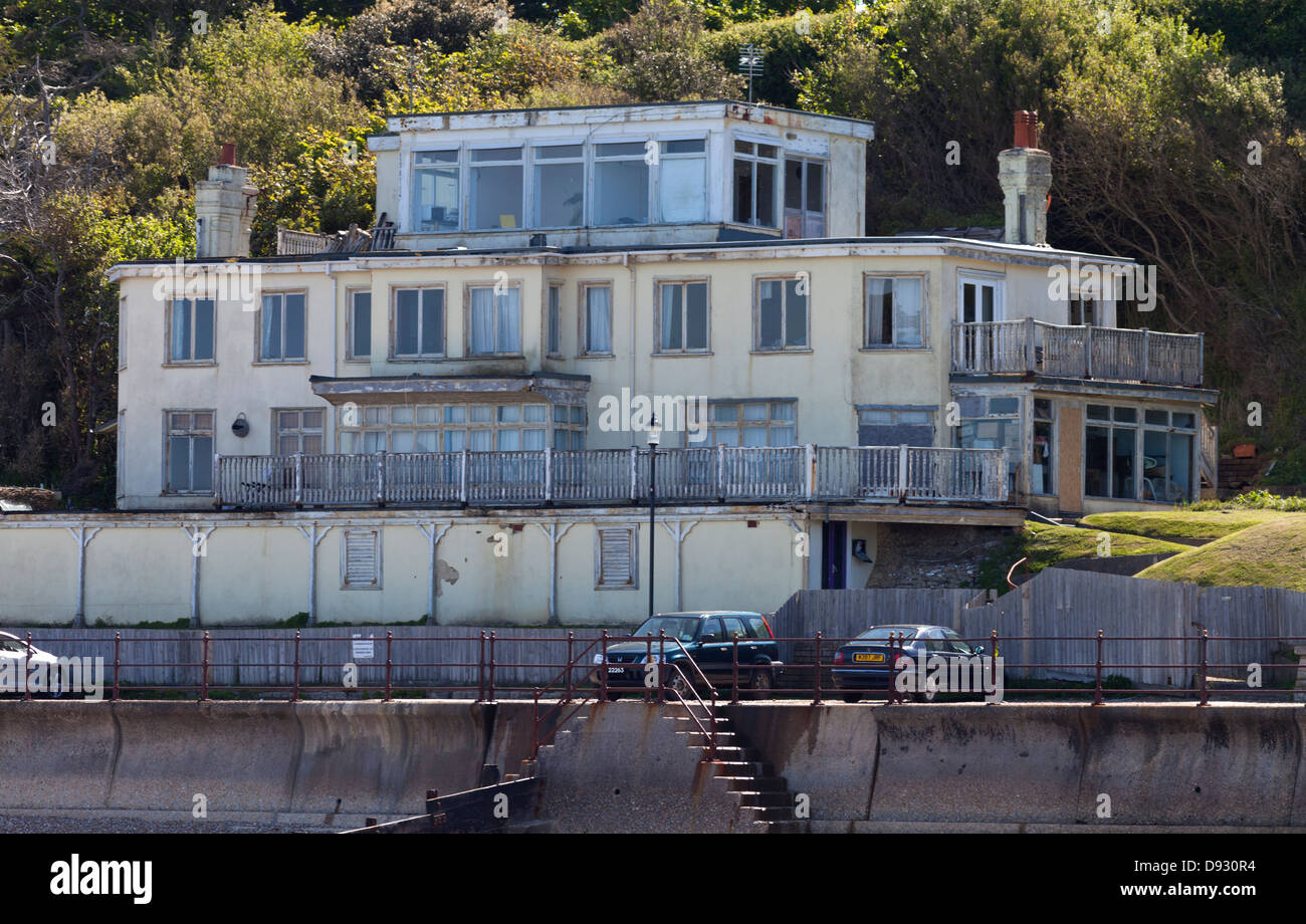 Run down dilapidated disused seaside old hotel Totland Bay Isle of Wight above promenade - Stock Image
