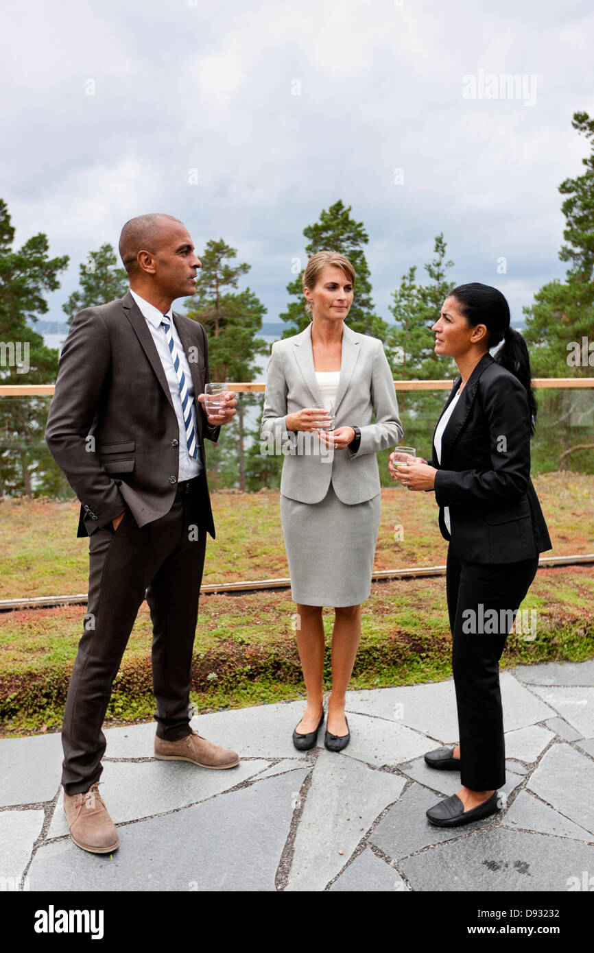 Businessman and businesswomen discussing outdoors - Stock Image