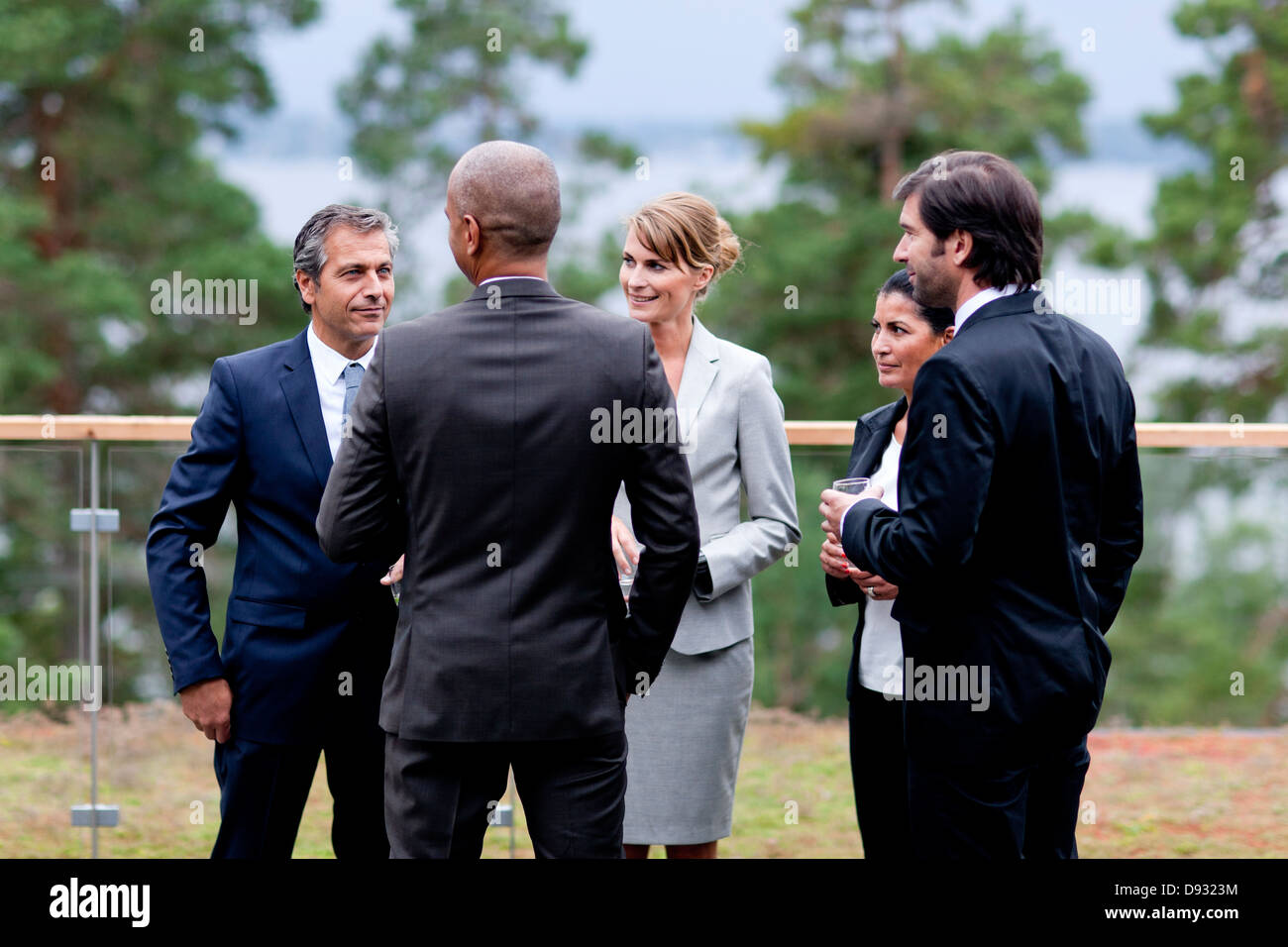 Businessmen and businesswomen discussing outdoors - Stock Image