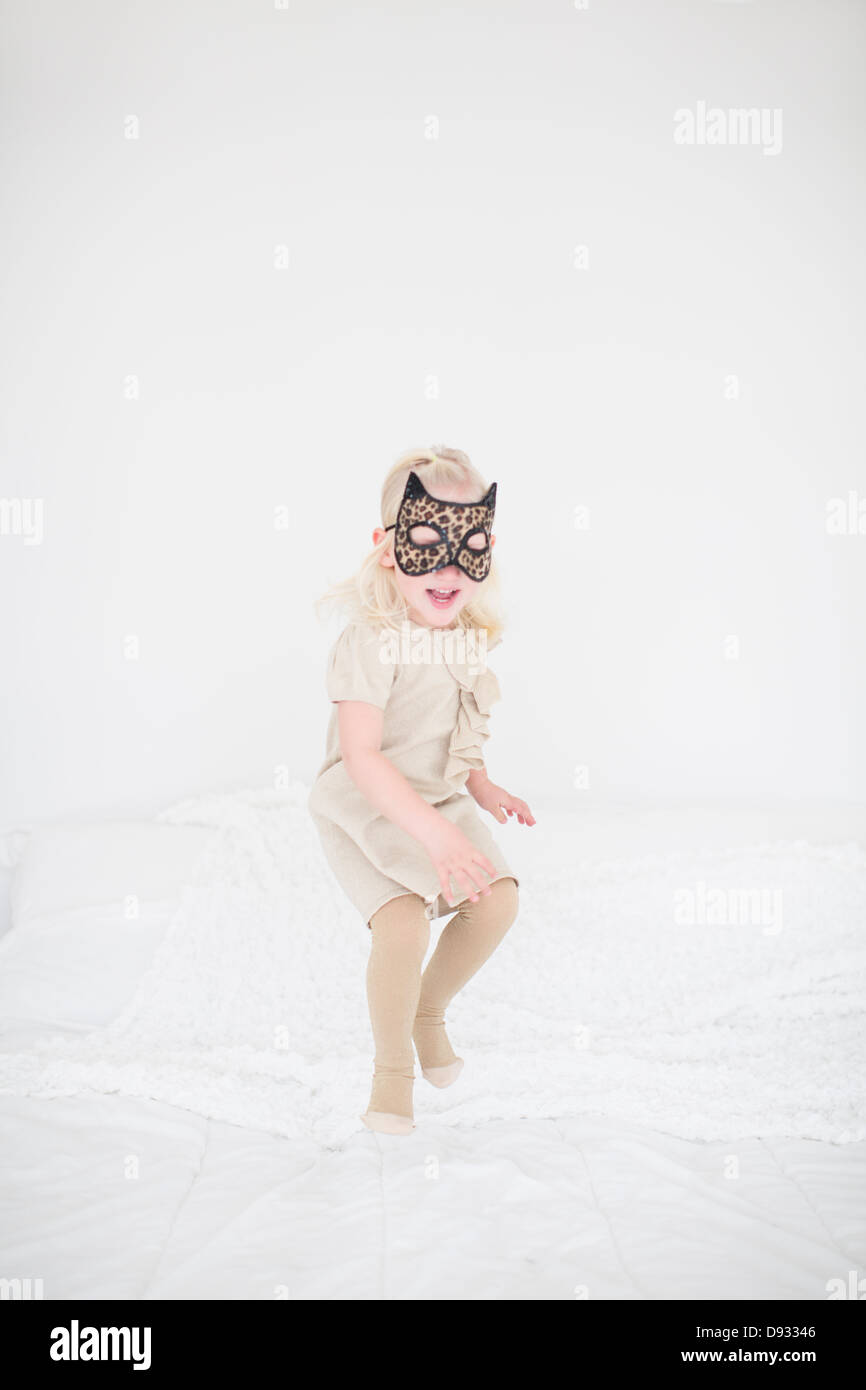 Girl wearing cat mask jumping on bed - Stock Image