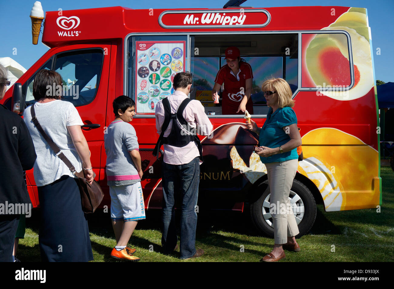 Customers queuing for traditional Wall's Mr Whippy ice cream, from a parked vehicle, outside on a hot summer - Stock Image