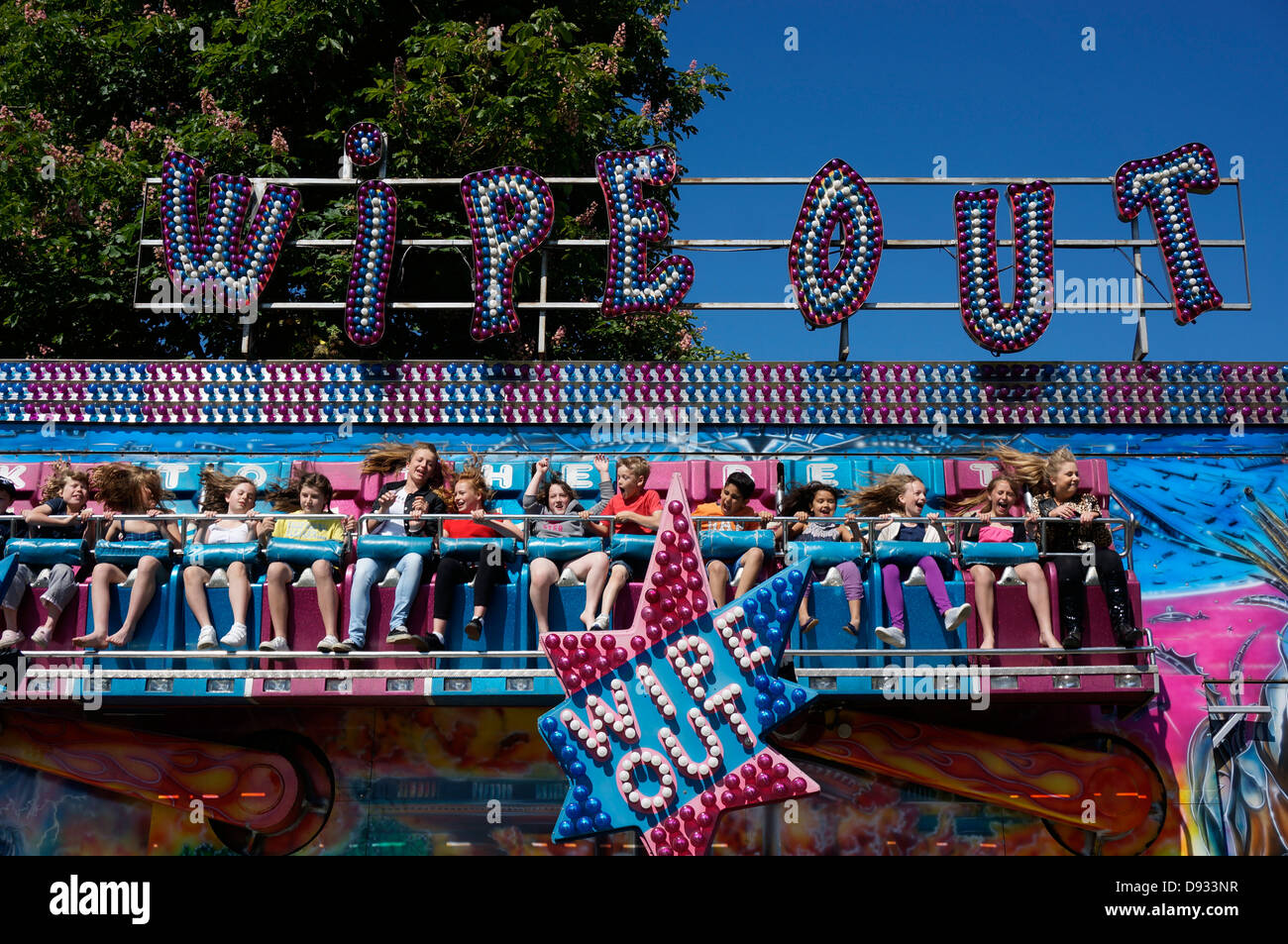 Noisy teenagers sitting down and secured in place, enjoying the Wipe Out thrill ride, at an outdoor summer fair. - Stock Image