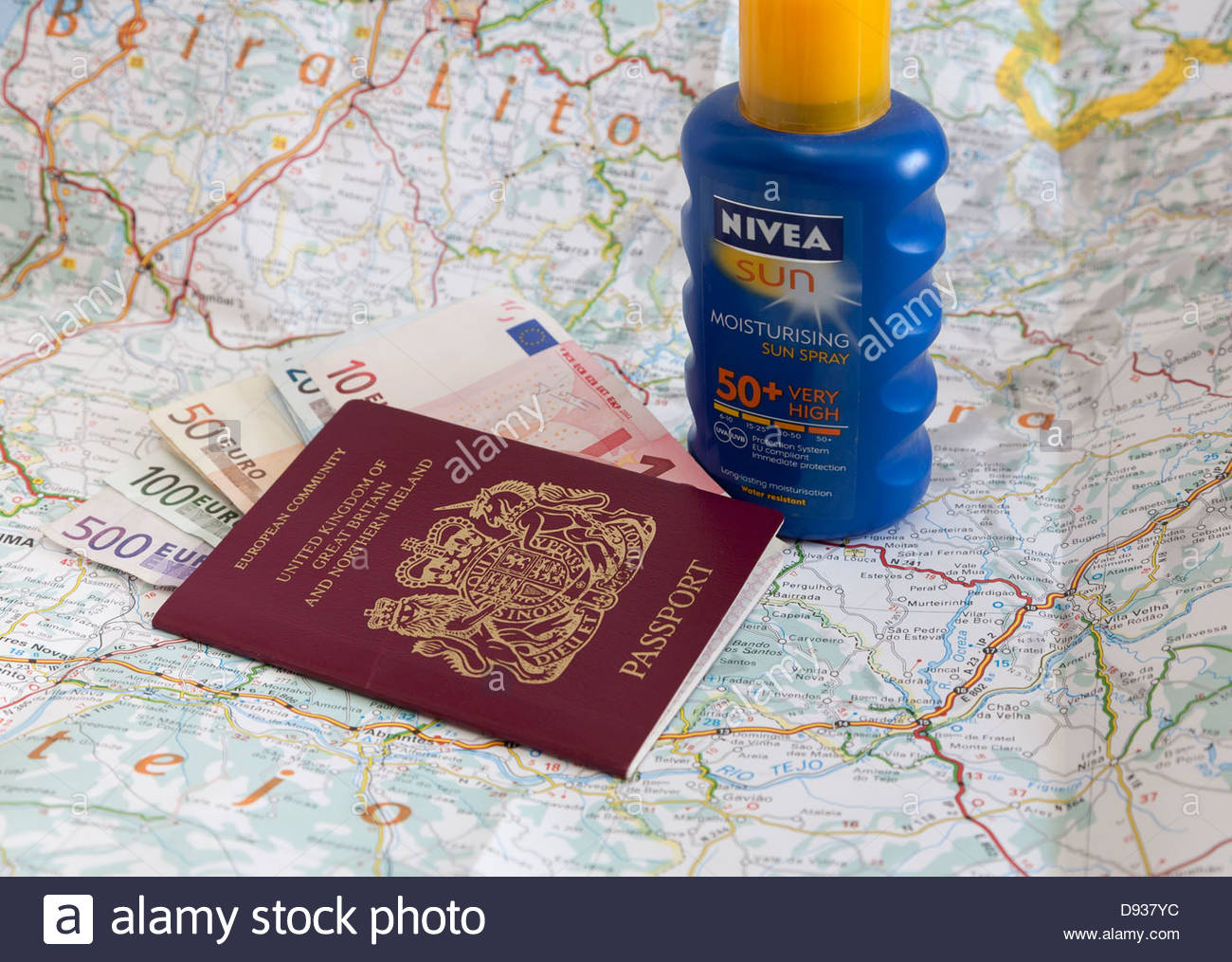 British passport, euro notes, bottle of sun screen and an open map of Portugal - Stock Image