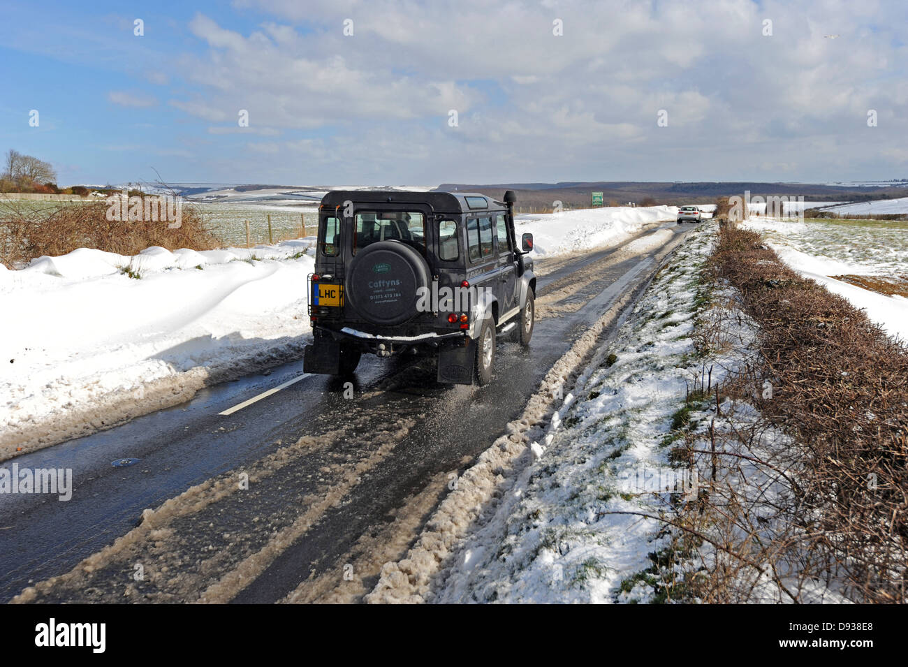 A Land Rover drives on the road after a heavy snowfall on the Sussex Downs - Stock Image