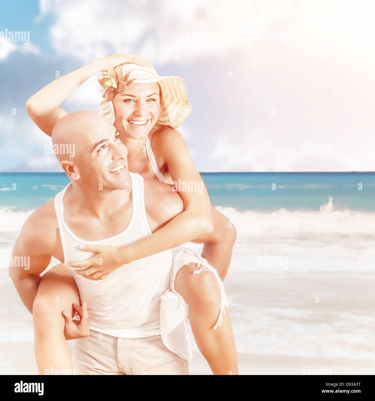 Happy couple on the beach, handsome man piggy back attractive woman, romantic date on seashore, luxury summer resort - Stock Image