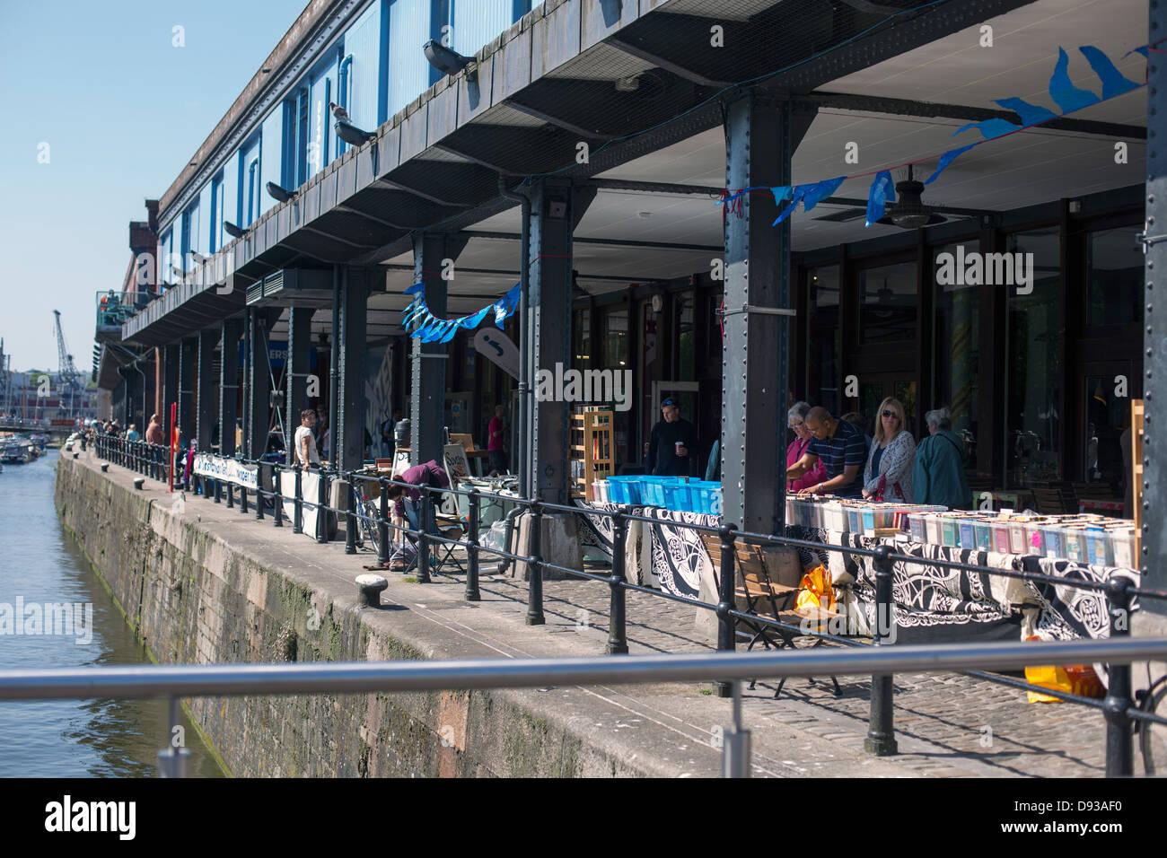 Bristol Harbourside market under Watershed building - Stock Image