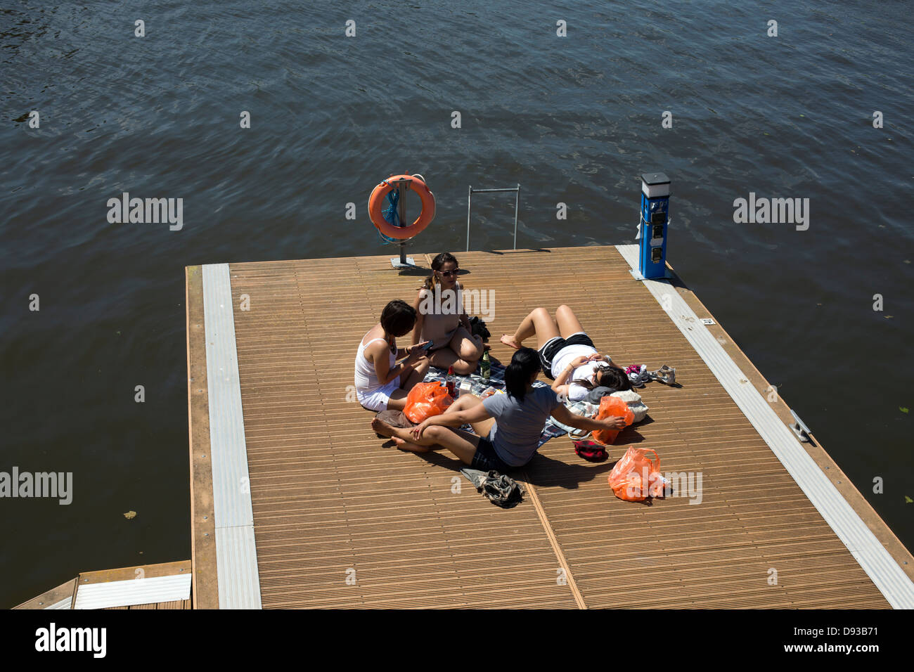 Bristol Harbourside Young people sunbathing picnicking on jetty of Avon river - Stock Image