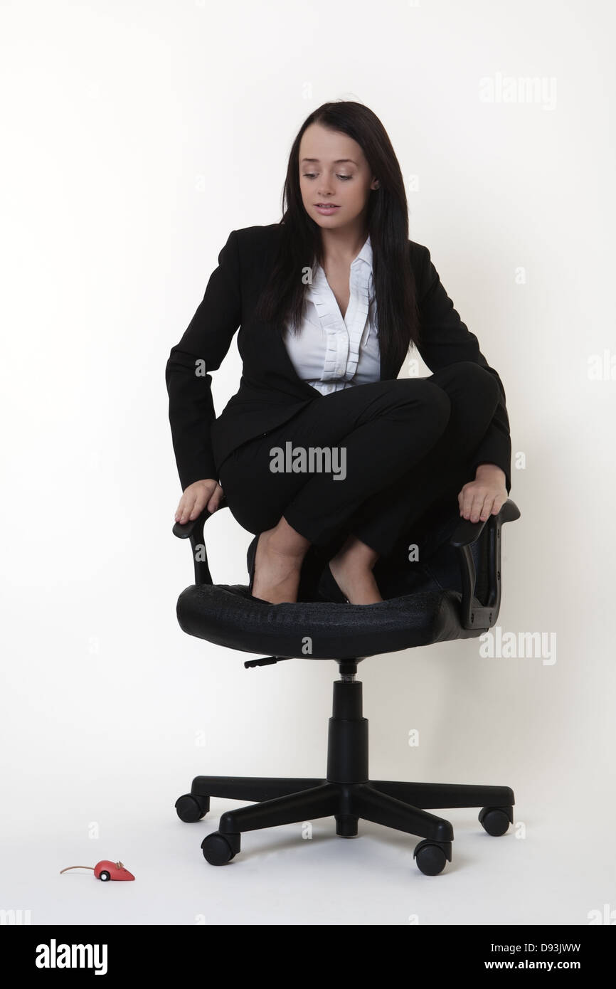 business woman who doesn't like mice crouched on an office chair as a toy mouse runs around on the floor - Stock Image