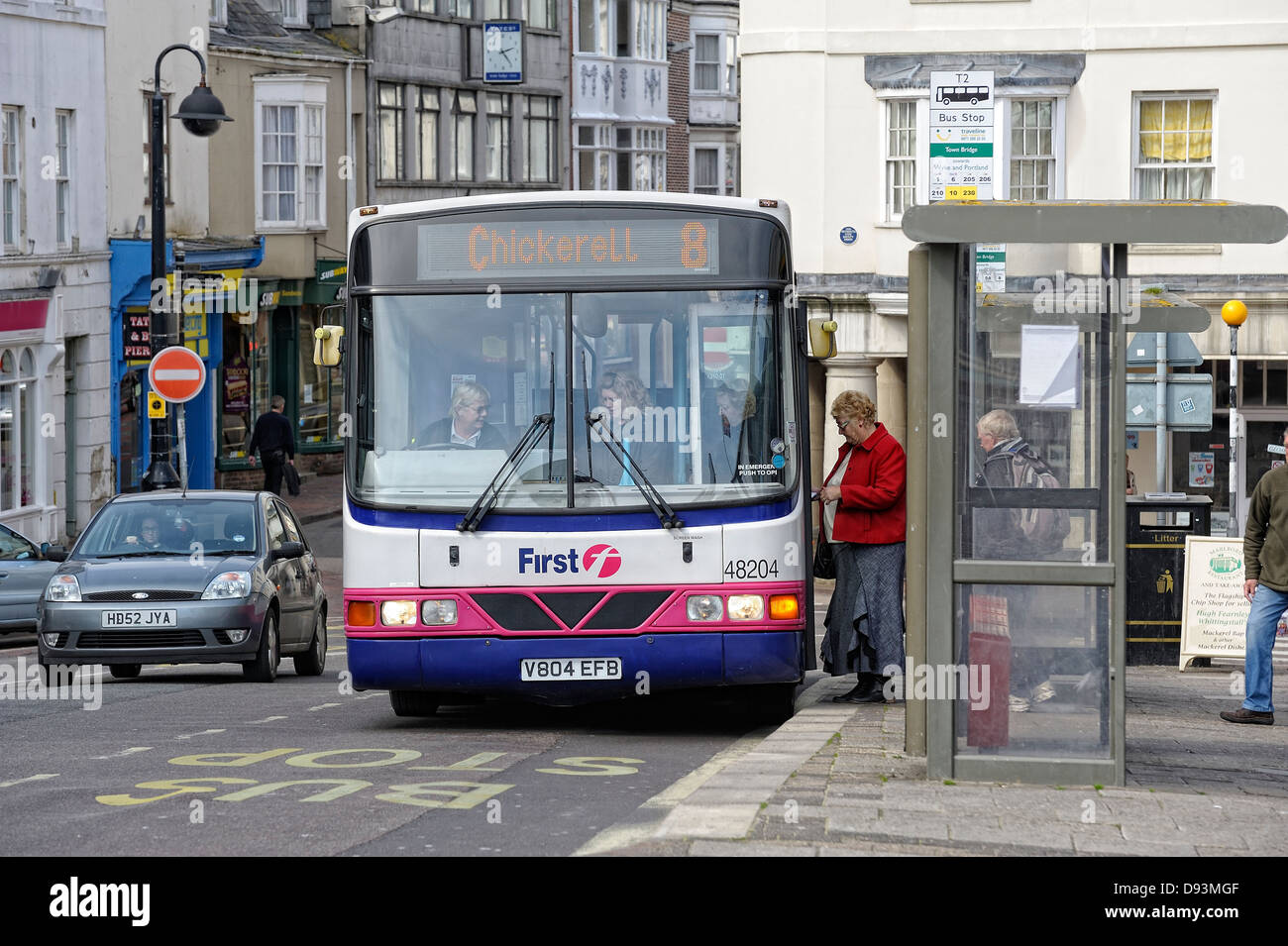 Passengers boarding a bus at a bus stop Weymouth Dorset England uk Stock Photo