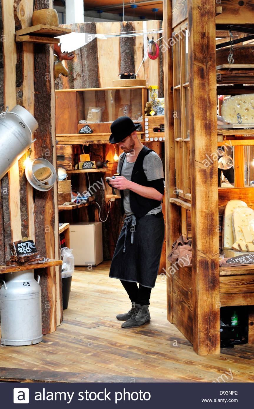 An employee in a cheeses shop checks his mobile phone. Borough market, London, UK - Stock Image