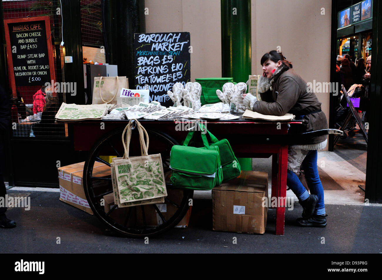 A woman selling shopping bags and aprons from a cart in Borough market, London, UK. - Stock Image