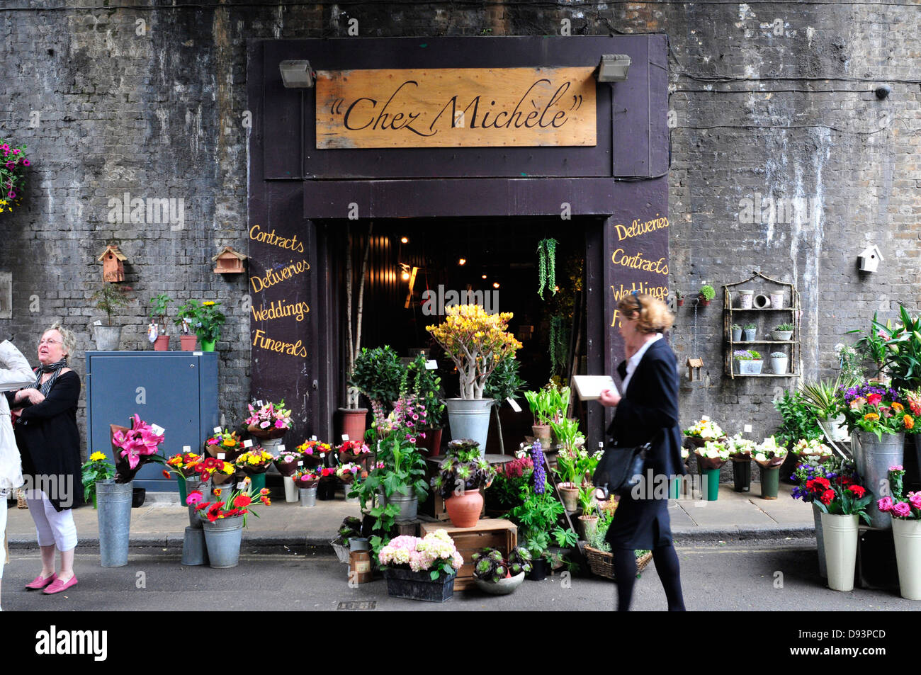 A woman walks past a flower shop next  to Borough market, London, UK - Stock Image