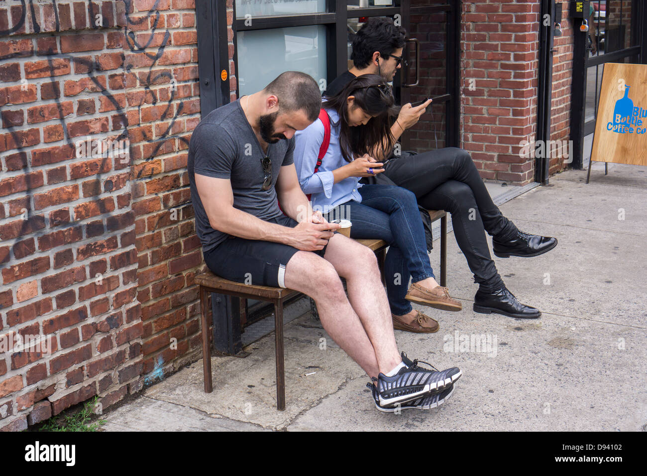 Hipsters preoccupied with their smartphones outside a coffee shop in the trendy hipster Williamsburg neighborhood - Stock Image